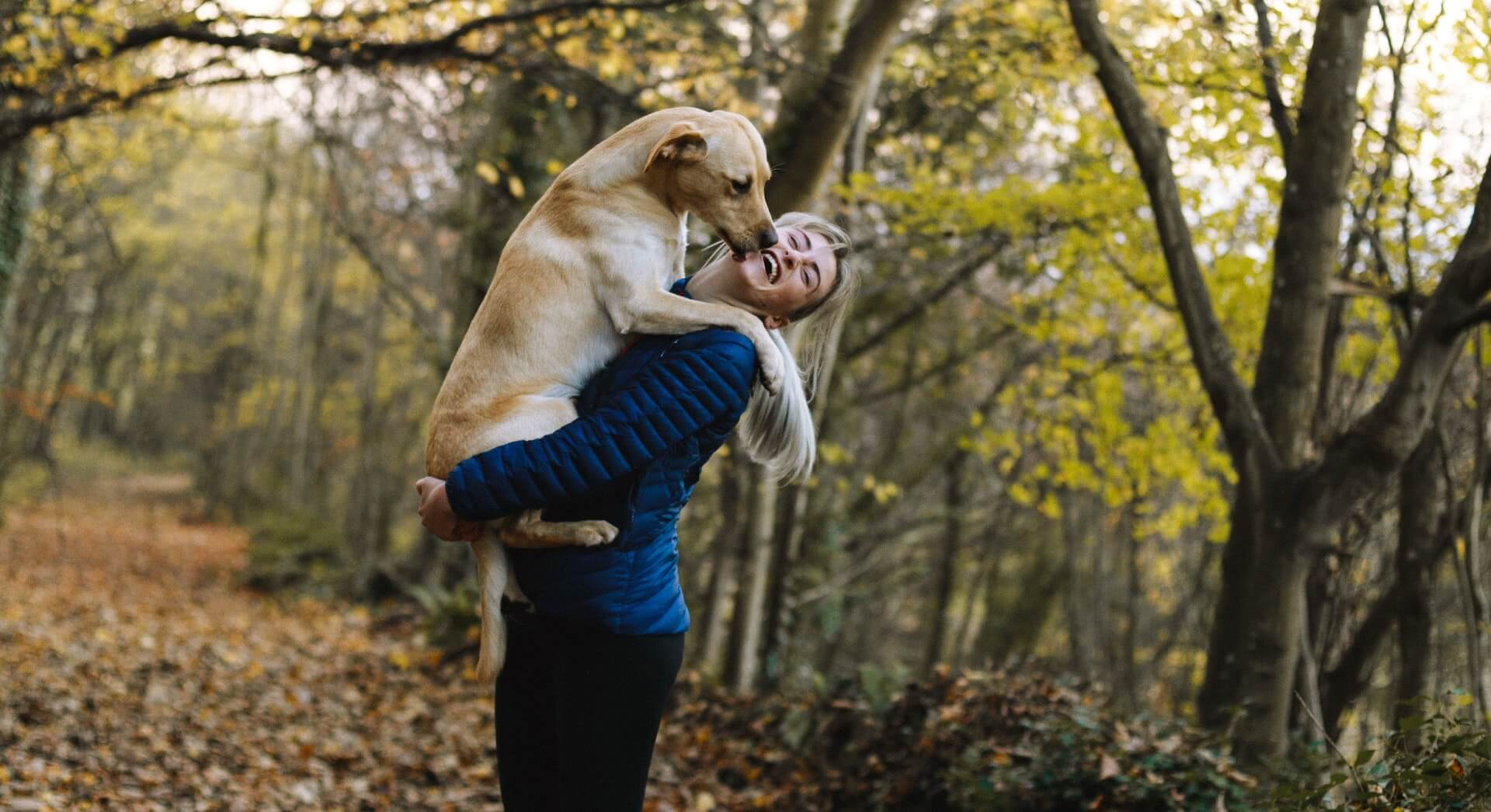 Donna a passeggio nel bosco con il suo cane
